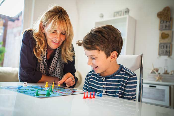 woman playing board game with boy