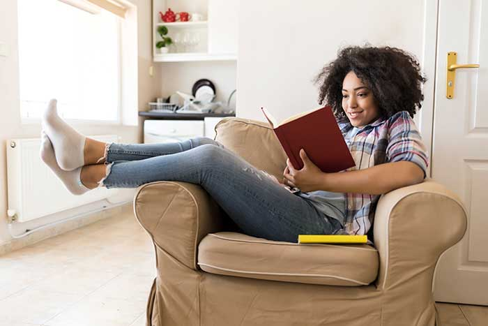 girl reading a book in armchair